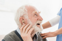 Profile Of Happy And Cheerful Man With Hearing Aid In Ear, Looking Away