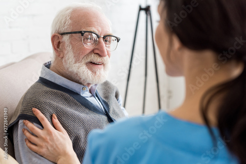 Obraz Selective focus of cheerful and grey haired man looking at nurse - fototapety do salonu