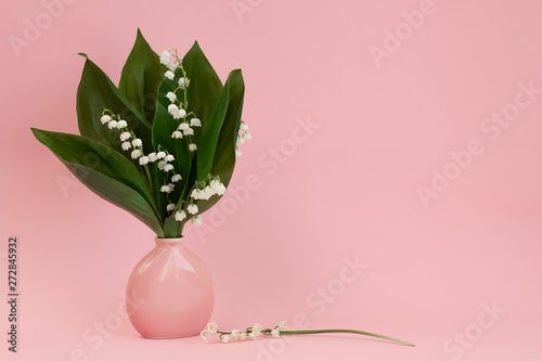 Bouquet of lilies of the valley in a pink vase on a pink background