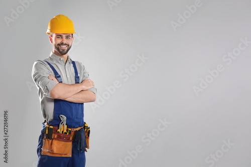 Fotografia Portrait of professional construction worker with tool belt on grey background,