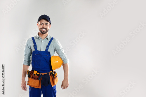Obraz Portrait of construction worker with hard hat and tool belt on light background, space for text - fototapety do salonu