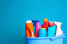 Plastic Bucket With Different Cleaning Products Against Color Background. Space For Text