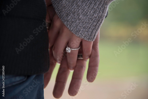 Fotografie, Obraz  ENGAGED COUPLE HOLDING HANDS