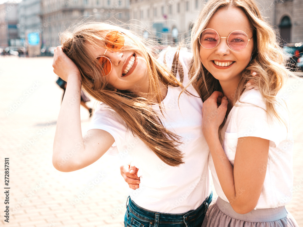 Fototapety, obrazy: Portrait of two young beautiful blond smiling hipster girls in trendy summer white t-shirt clothes. Sexy carefree women posing on street background. Positive models having fun in sunglasses.Hugging