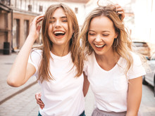 Portrait Of Two Young Beautiful Blond Smiling Hipster Girls In Trendy Summer White T-shirt Clothes. Sexy Carefree Women Posing On Street Background. Positive Models Having Fun.Hugging