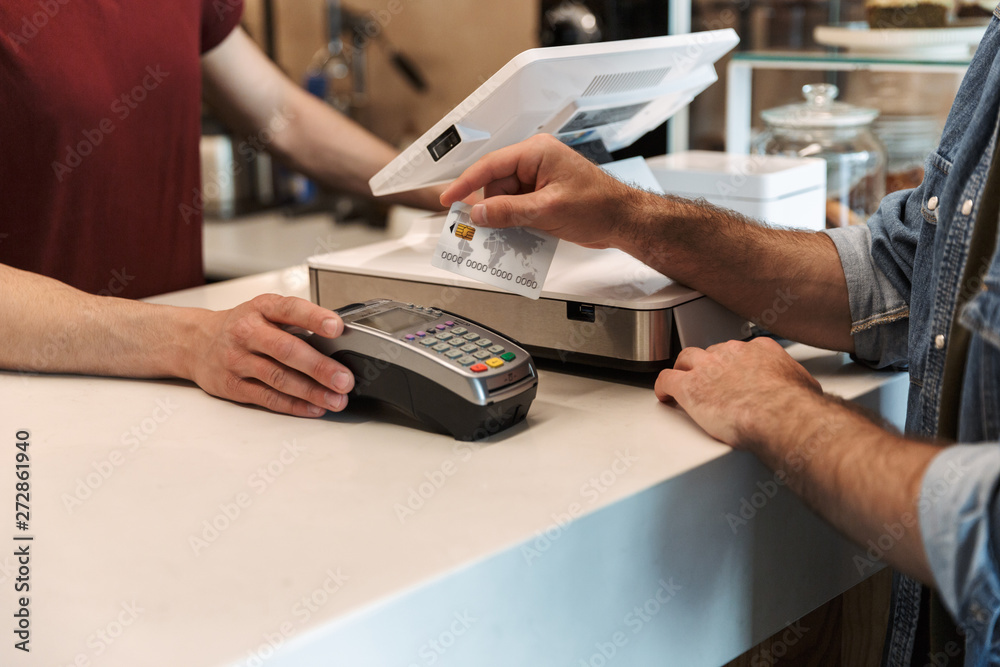 Fototapeta Cropped photo of caucasian man paying debit card in cafe while waiter holding payment terminal