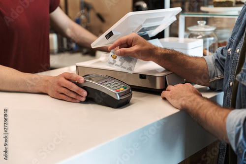 Photo Cropped photo of caucasian man paying debit card in cafe while waiter holding pa