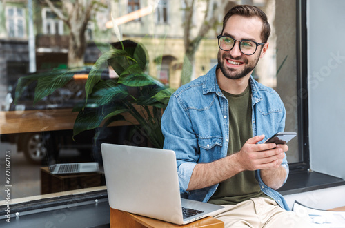 obraz dibond Photo of successful young man holding smartphone while working on laptop in city cafe outdoors