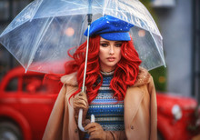 Spectacular Girl In A Beret With Red Hair, Hiding Under A Transparent Umbrella, On The Background Of A Red Car