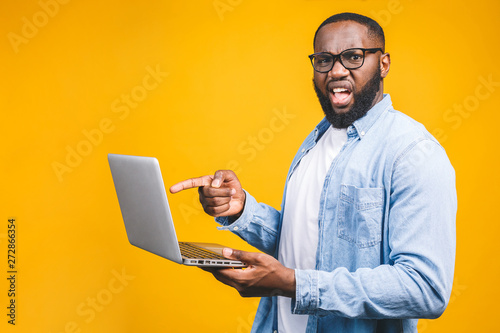 Fotografía  African american ypung man scared a bad news on his laptop, isolated against yellow background