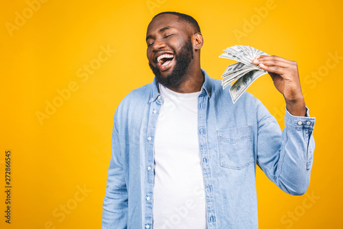 Pinturas sobre lienzo  Winner! Young rich african american man in casual t-shirt holding money dollar bills with surprise isolated over yellow wall
