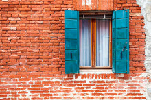 Window With Blue Shutters On The Old Red Brick Wall. Burano Island, Venice, Italy.