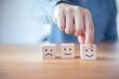 Leinwandbild Motiv Close up customer hand choose smiley face and blurred sad face icon on wood cube, Service rating, satisfaction concept.