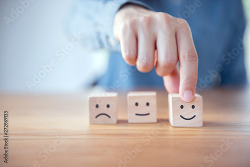 Fotografia  Close up customer hand choose smiley face and blurred sad face icon on wood cube, Service rating, satisfaction concept