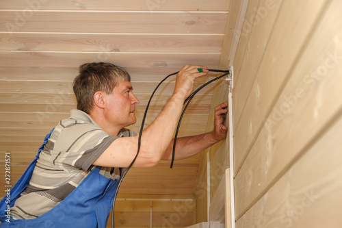 electrical engineer performs installation of electrical wiring inside a  wooden house  laying wires on the walls in the cable channel