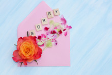 Word Sorry, Flowers And Envelope On Blue Background.