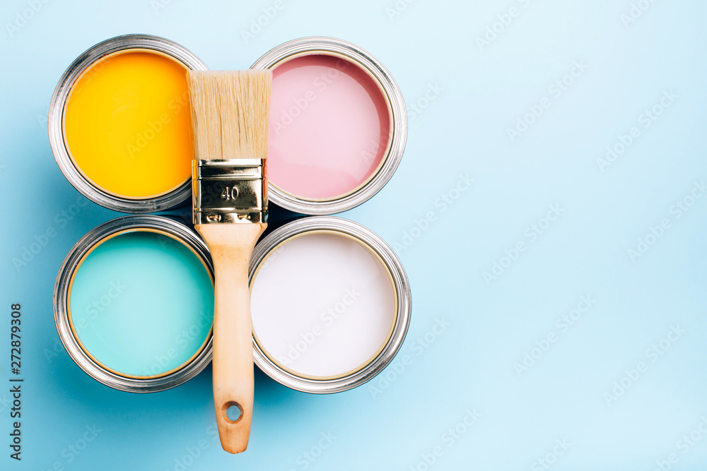 Fototapety, obrazy: Brush with wooden handle on open cans on blue pastel background. Yellow, white, pink, turquoise colors. Renovation concept. Place for text.