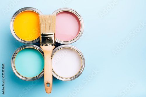 Brush with wooden handle on open cans on blue pastel background Фотошпалери
