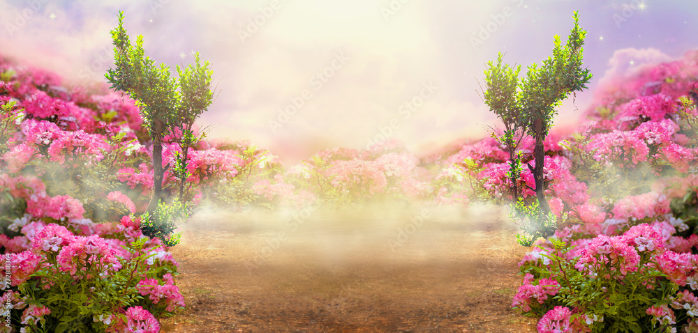 Fantasy summer panoramic photo background with rose field, trees and misty path leading to mysterious glow. Idyllic tranquil morning scene and empty copy space. Road goes across hills to fairytale.