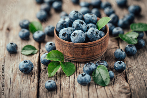 Freshly picked blueberries in wooden bowl on wooden background. Healthy eating and nutrition. - 272899168