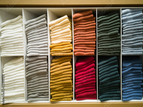 Fotografia, Obraz  Cotton T-shirt folded neatly in the showroom,Colorful clothes folded in the cabinet,Colorful clothes neatly dressed,Shelves and multi-colored clothes in large stores,A row of colorful shirts