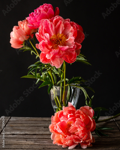Bright pink peonies in a glass vase on a rustic slotted table with a black background Canvas Print