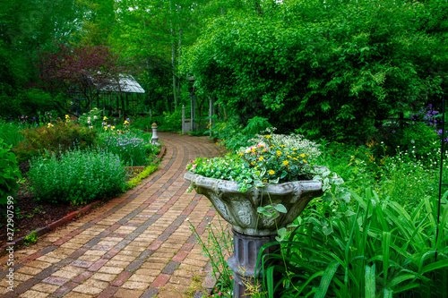 Spoed Fotobehang Groene Flowers in Urn by Brick Pathway