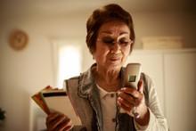 通帳を持ち携帯電話を見るシニア女性