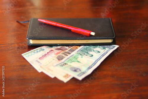 Poster Chicken Lao currency banknotes, pen, and savings notebook laying on wooden table - Lao Kip banknotes saving with a notebook for take notes the savings as daily diary - money savings concept