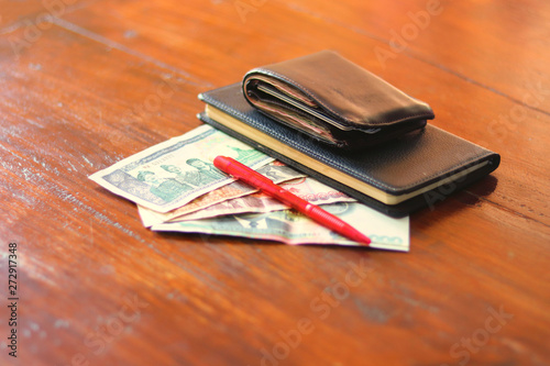 In de dag Kip Lao currency banknotes, pen, savings diary book and wallet laying on wooden table - Lao Kip banknotes for savings with a notebook for noting the savings as daily diary - money savings concept