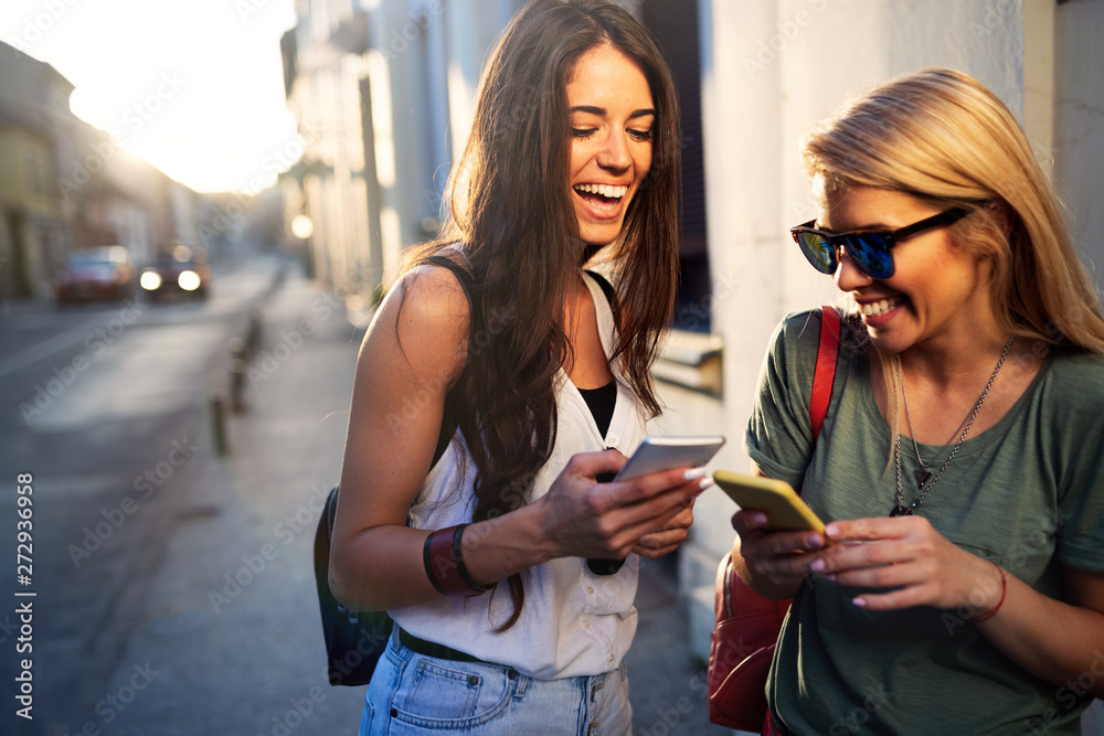 Fototapeta young pretty woman friends posing in the street with phone