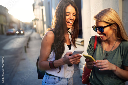 young pretty woman friends posing in the street with phone