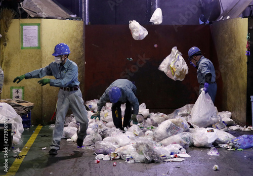 Workers sort out plastic waste for recycling at Minato
