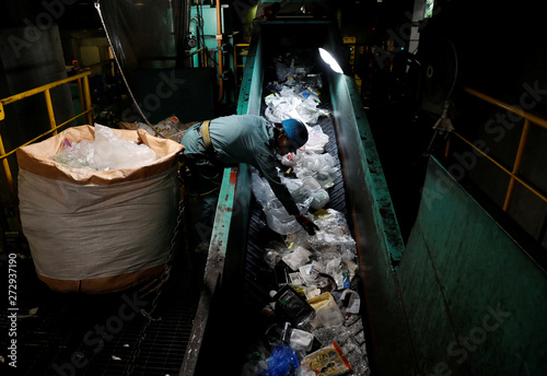 A worker sorts out plastic waste for recycling at Minato