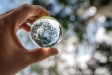 Reflection of blue sky, white clouds and trees in a glass ball in holding hand