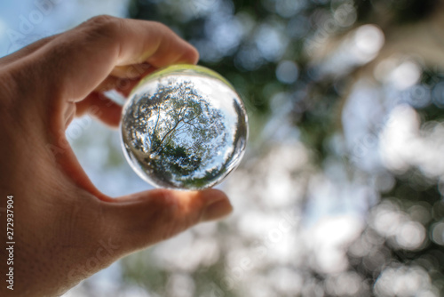 Stampa su Tela Reflection of blue sky, white clouds and trees in a glass ball in holding hand