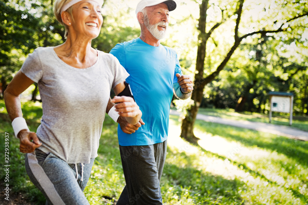 Fototapeta Mature couple jogging and running outdoors in city