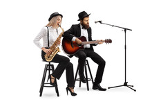 Young Woman Playing Sax And A Man Playing An Acoustic Guitar
