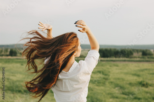 Close up portrait of beautiful carefree long hair girl in white clothes in field, view from back. Sensitivity to nature concept