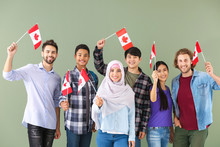 Group Of Students With Canadian Flags On Color Background