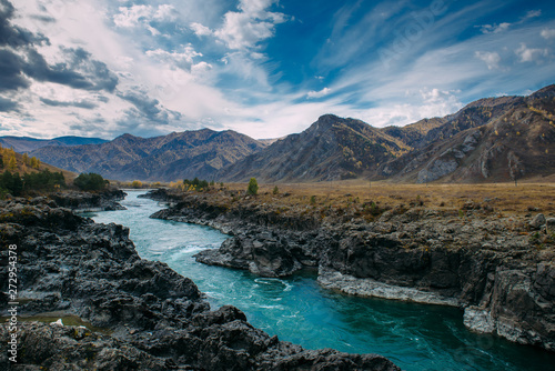 Foto op Plexiglas Blauw Turquoise Katun river in gorge is surrounded by high mountains under majestic autumn sky. A stormy mountain stream runs among rocks - landscape of the Altai mountains, beautiful places of the planet.
