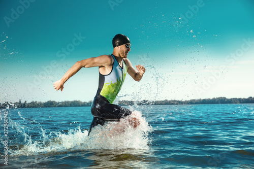 Fototapeta Professional triathlete swimming in river's open water