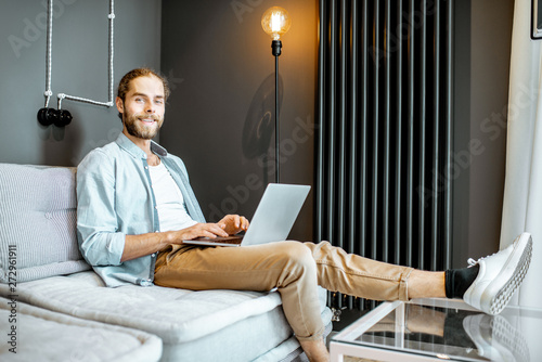 Canvas Prints Textures Man working with laptop while sitting on the couch in the living room at home
