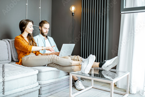 Canvas Prints Textures Young couple sitting on the couch with laptop in the living room at home