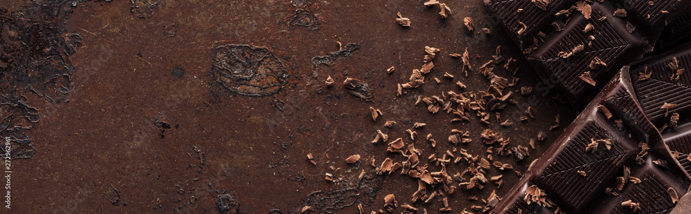 Fototapety, obrazy: Panoramic shot of pieces of chocolate bar with chocolate chips on metal background