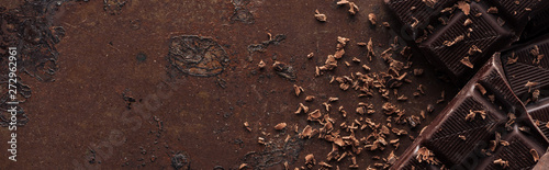 In de dag Chocolade Panoramic shot of pieces of chocolate bar with chocolate chips on metal background