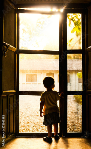 Backlit toddler standing in front of mosquito net door in Chitwan, Nepal
