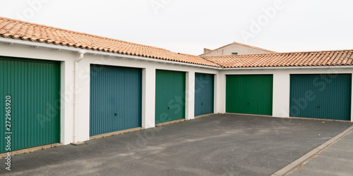 Obraz na plátne Row of green parking garage doors in parking area for apartment and home suburb
