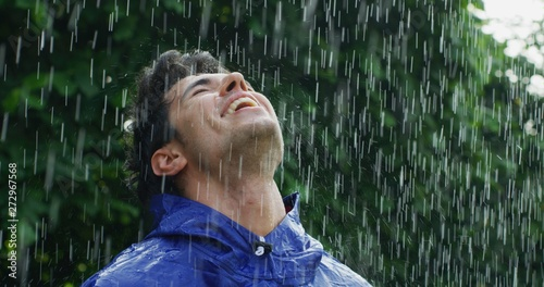 Portrait of young carefree handsome young man wearing protection cape is feeling free under the rain on a background of green trees Fototapete