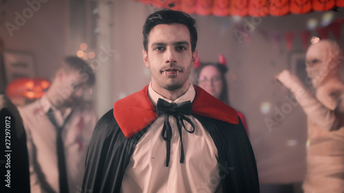 Halloween Costume Party Portrait Of Count Dracula Smiling Creepily Shows His Deadly Bloody Fangs In The Background Retro Lit Decorated Room With Scary Monsters Dancing Buy This Stock Photo And Explore